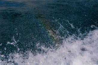 Радуга в брызгах воды от лодки.